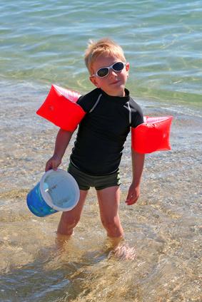 Petit garçon en combinaison anti-UV plage