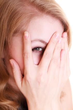 Femme avec couperose qui la cache avec ses mains