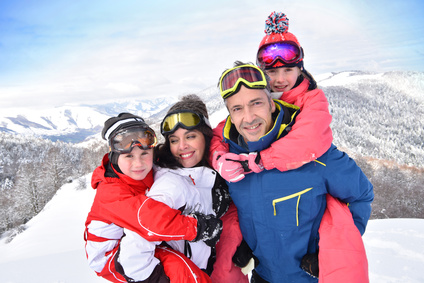 Parents et enfants debout dans la neige aux sports d'hiver