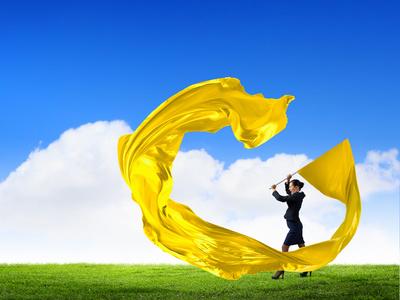 Femme agitant une bannière jaune dans un pré