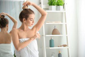 Femme qui se met du déodorant