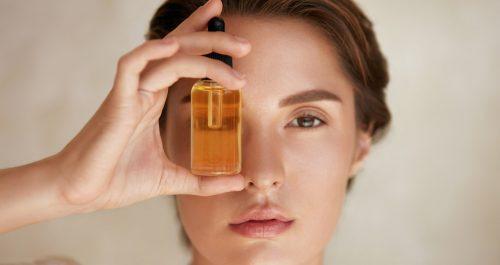 femme tenant un sérum d'huiles hydratantes