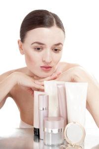 Jeune Femme perplexe devant un choix de cosmétiques