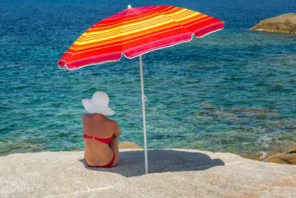 Femme à l'abri d'un parasol regarde la mer