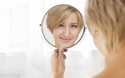 Femme qui sz regarde dans un miroir