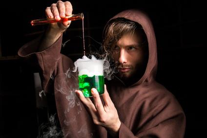 Un moine verse un liquide rouge dans un liquide vert qui fume