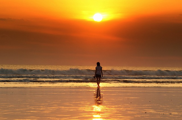 Coucher de soleil sur une plage avec jeune femme à l'horizon