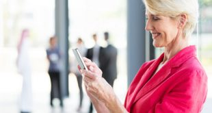 Femme mature en veste rose tenant un téléphone mobile