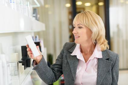 Femme tenant une crème et lisant la composition d'un cosmétique