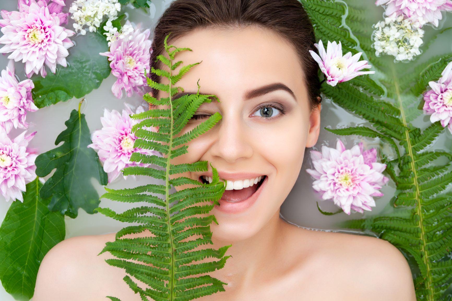 femme dans un bain avec des feuilles et fleurs