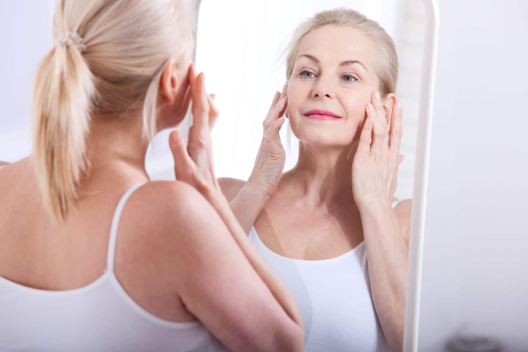 reflet d'une femme dans mirroir qui regarde les signes de l'age