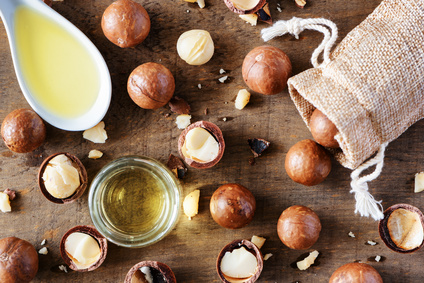 Macadamia nuts and natural macadamia oil on wooden board